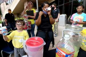 Luke Sutton's mother Danielle Sutton (back) laughs as Luke asks to taste the winning entry - his own - as Misty Nix samples the concoctions during the Lemonade Day Best Tasting Contest Tuesday at the Christus Health and Wellness Center. Photo made Tuesday, April 27, 2021 Kim Brent/The Enterprise