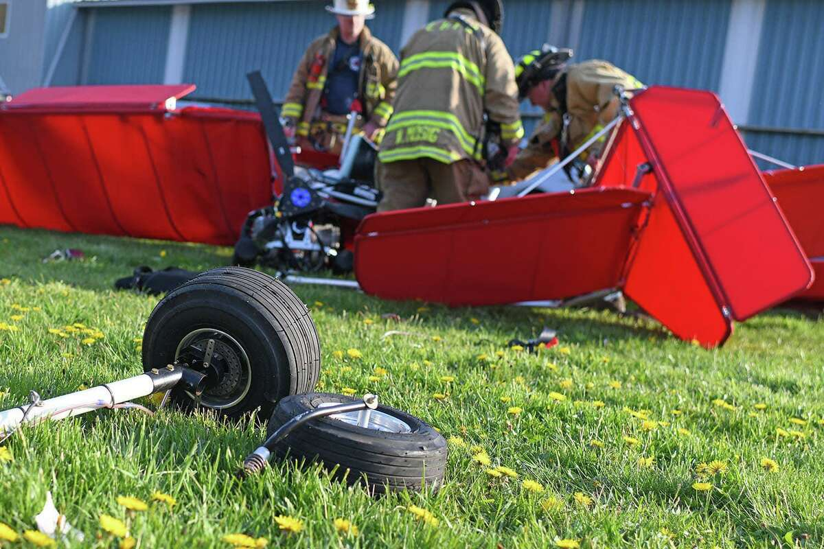 First responders were dispatched to a plane crash near Goodspeed Airport Tuesday evening, April 27, 2021, in East Haddam, Conn. State police said the ultralight aircraft was picked up by a gust of wind before it crash landed behind one of the airport hangers.