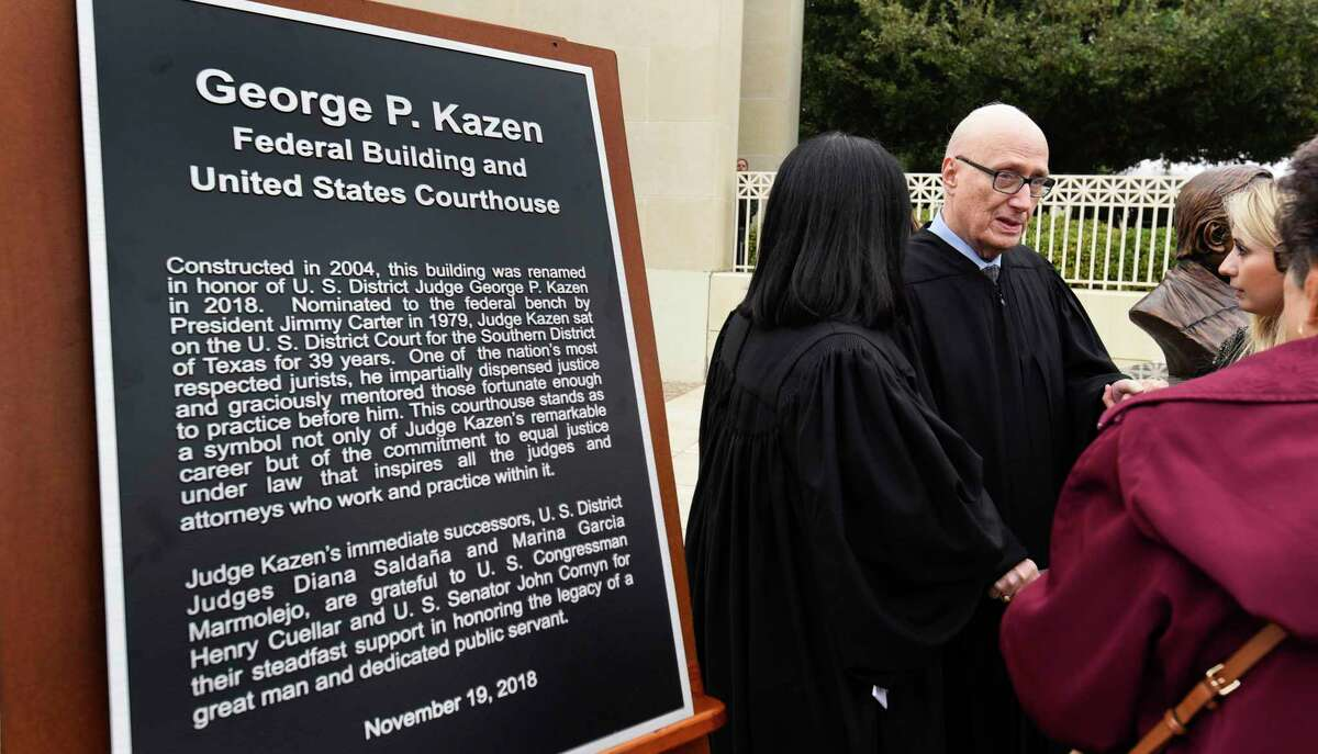 In this Nov. 19, 2018 photo, a plaque commemorating retired U.S. distrit judge George P. Kazen is displayed as Kazen is congratulated after a ceremony renaming the federal courthouse to the George P. Kazen Federal Building and United States Courthouse.