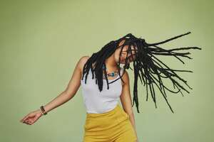 Shot of an attractive young woman dancing against a green background with her dreadlocks.