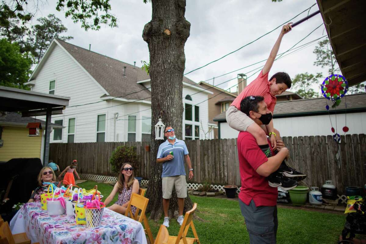 Logan Miller, 9, uses a pole to try to get a piece of a toy back from the roof of a shed during an outdoor family Easter gathering, Sunday, April 4, 2021, in Houston.