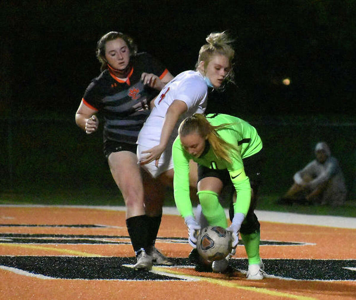 Alton keeper Addison Miller scoops up the ball in front of defender Taylor Freer and an Edwardsville forward in the second half on Tuesday in Edwardsville.