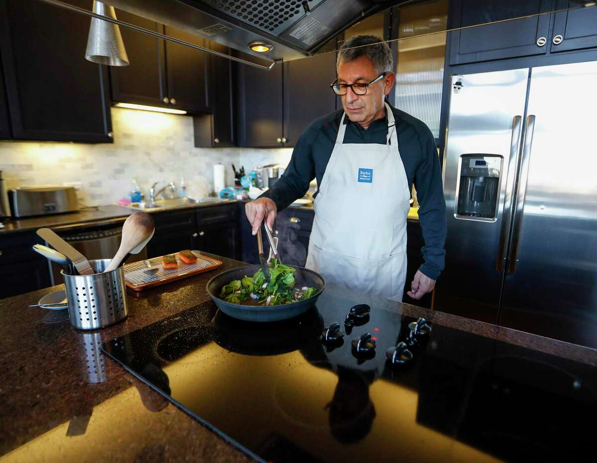 Dr. Paul Klotman, president and CEO of Baylor College of Medicine, cooks spinach and onion to go with his crispy salmon, in his kitchen, Thursday, March 18, 2021. Pre-covid, he was at a fine dining restaurant every night of the week. Xochi, Brennan's, DeMarco's and then his favorites in Manhattan, where he lives part of the month with his wife. Then the pandemic happened and it all changed. He had a bottle of wine and milk in his refrigerator. In the last year, Klotman has been sous vide cooking, he makes bread, he pickles vegetables and has started his own herb garden on his balcony. He took MasterClass cooking classes and orders specialty fish for elaborate dishes he wants to recreate. Cooking has become one of his outlets for stress relief, but he's looking forward to eating in more with friends and family once it's safe to do so.
