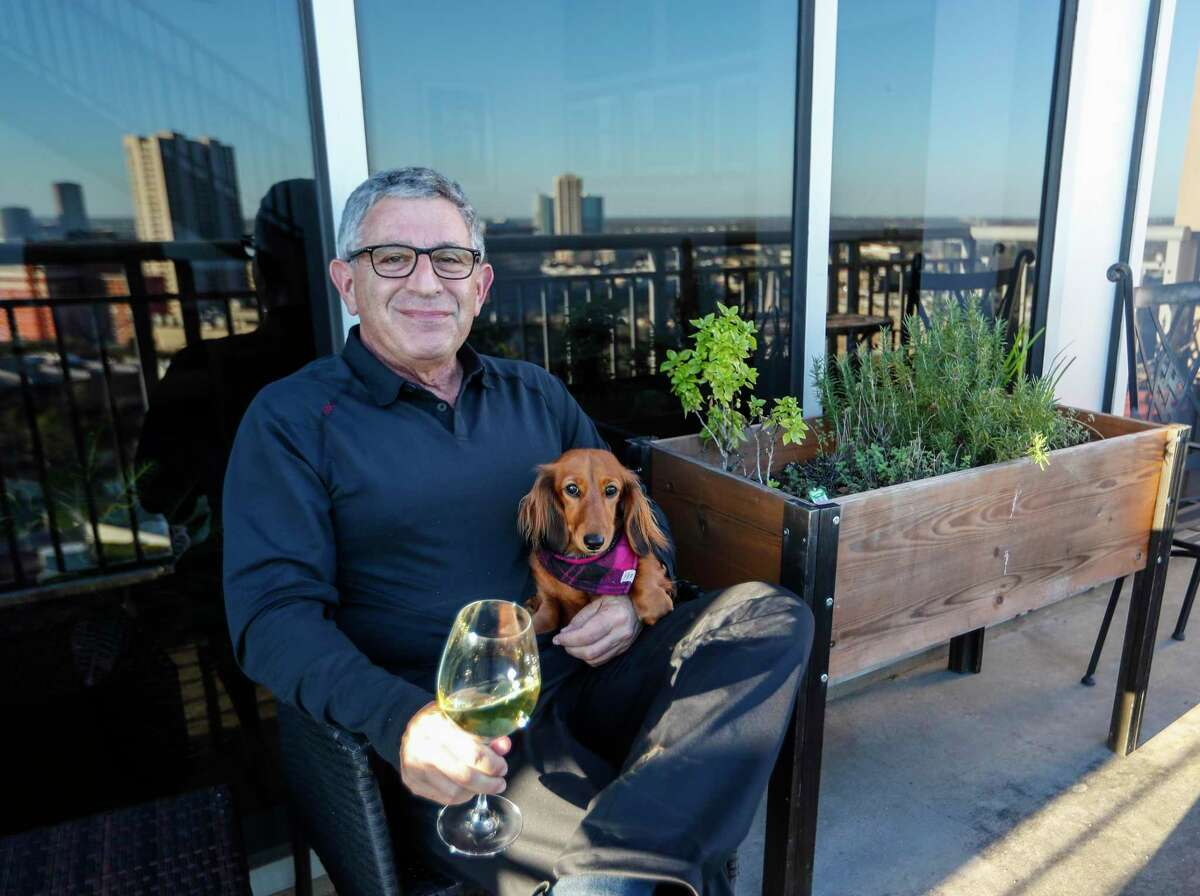 Dr. Paul Klotman, president and CEO of Baylor College of Medicine, sits with his dog, Lily as he enjoys a glass of wine next to his herb garden on his balcony, Thursday, March 18, 2021. Pre-covid, he was at a fine dining restaurant every night of the week. Xochi, Brennan's, DeMarco's and then his favorites in Manhattan, where he lives part of the month with his wife. Then the pandemic happened and it all changed. He had a bottle of wine and milk in his refrigerator. In the last year, Klotman has been sous vide cooking, he makes bread, he pickles vegetables and has started his own herb garden on his balcony. He took MasterClass cooking classes and orders specialty fish for elaborate dishes he wants to recreate. Cooking has become one of his outlets for stress relief, but he's looking forward to eating in more with friends and family once it's safe to do so.