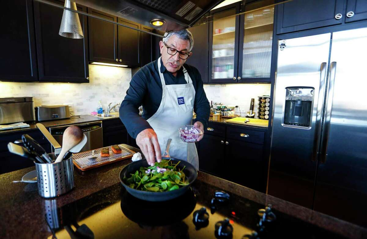Dr. Paul Klotman, Baylor College of Medicine president and CEO, cooks spinach, onion and crispy salmon in his kitchen.
