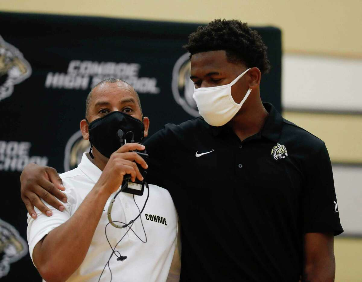 Shamar Levenstone, right, listens as head track coach JD Hurd speaks about him during an athletic signing ceremony at Conroe High School, Wednesday, April 28, 2021, in Conroe. Levenstone signed to run track for Northwest Kansas Tech College.