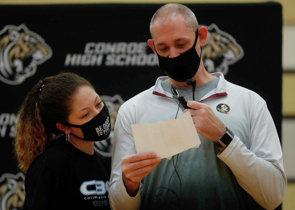 Amanda Rivera looks at a note from head volleyball coach Charvette Brown read by assistant coach Lonn Collins during an athletic signing ceremony at Conroe High School, Wednesday, April 28, 2021, in Conroe. Rivera signed to play volleyball for Columbia Basin College.