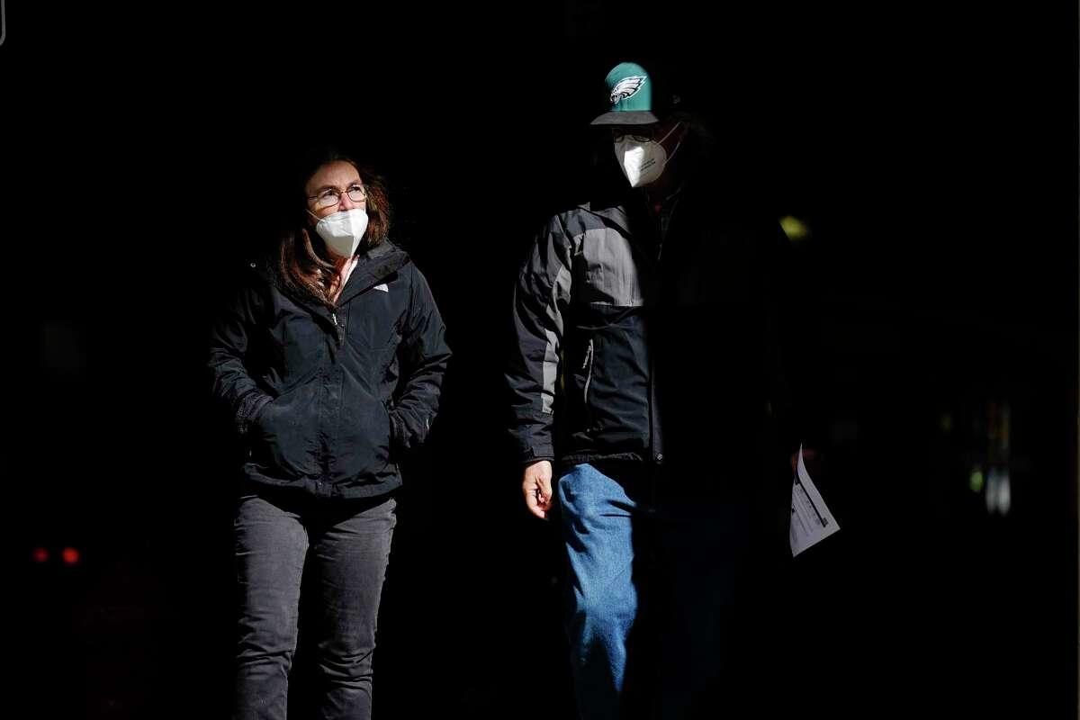 En esta foto de archivo del 3 de marzo de 2021, gente con mascarillas como precaución contra el coronavirus camina por una calle de Filadelfia. El martes 27 de abril de 2021, funcionarios de salud estadounidenses dijeron que la gente plenamente vacunada ya no necesita usar mascarillas en la calle al menos que se encuentre en grandes aglomeraciones.
