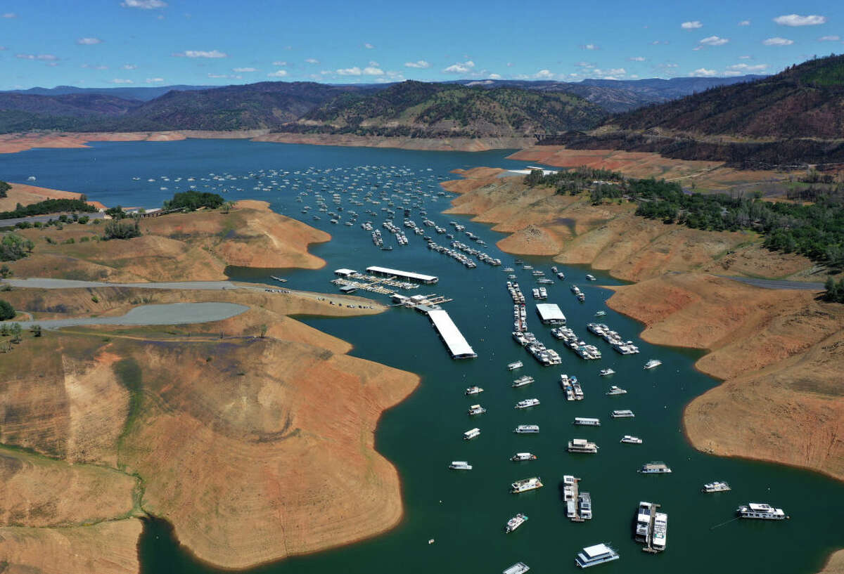 In an aerial view, houseboats are dwarfed by the steep banks of Lake Oroville on April 27.