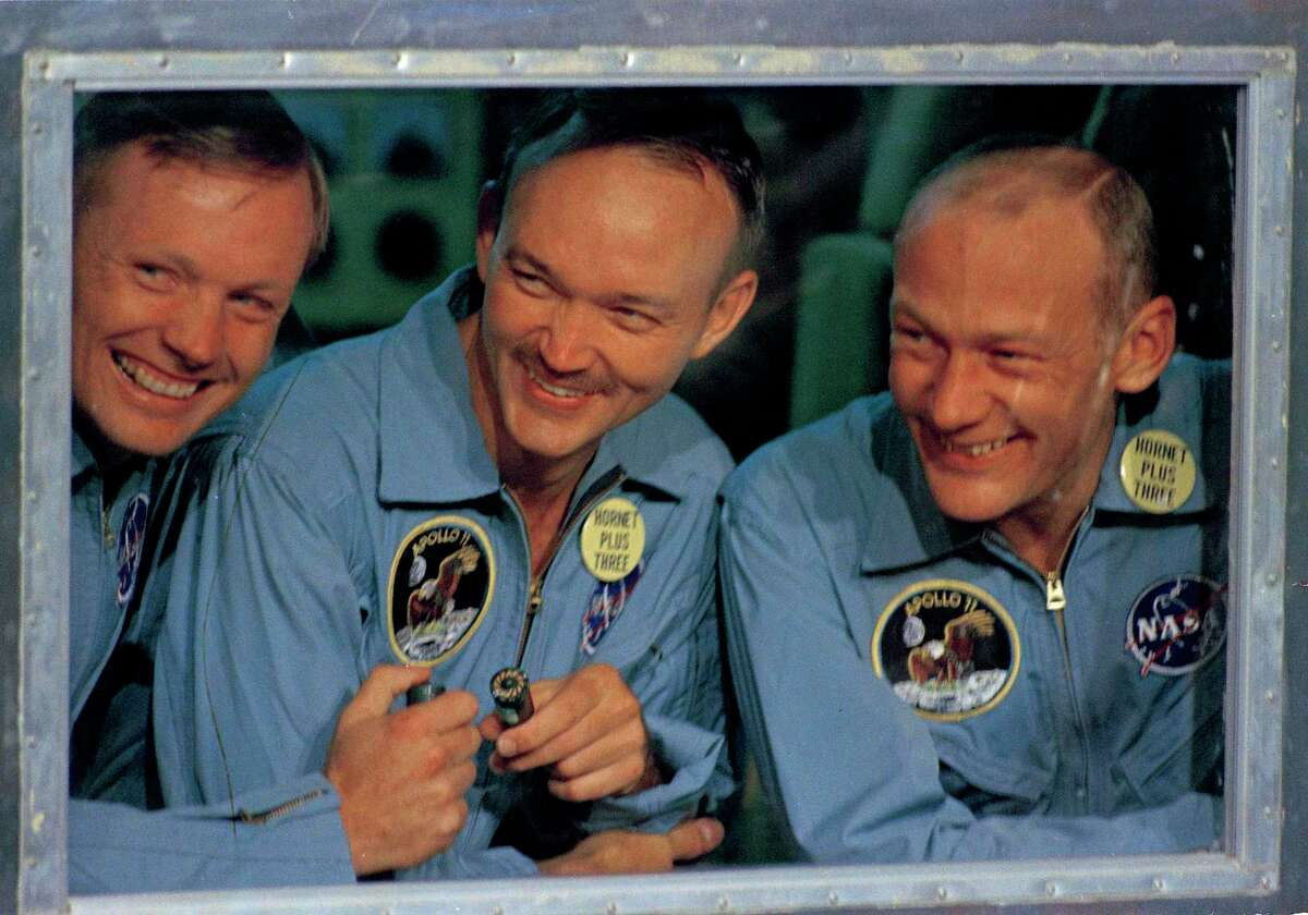 """In this July 24, 1969, file photo, Apollo 11 astronauts Neil Armstrong, left, Michael Collins, center, and Edwin """"Buzz"""" Aldrin answer questions from quarantine in an isolation unit aboard the USS Hornet after splashdown and recovery."""