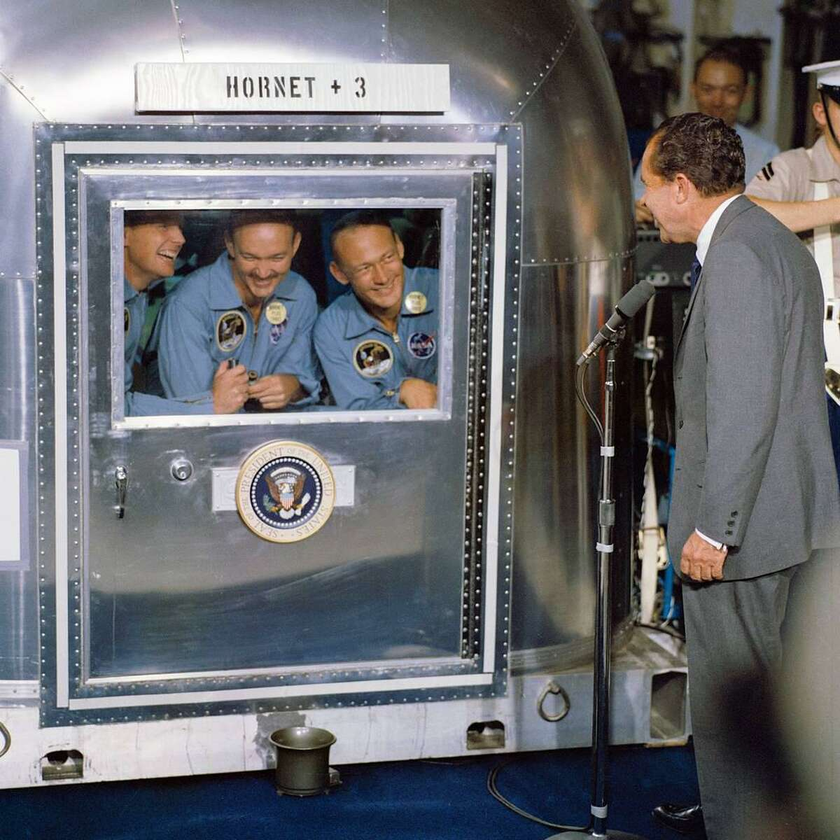 President Richard M. Nixon was in the central Pacific recovery area to welcome the Apollo 11 astronauts aboard the USS Hornet, prime recovery ship for the historic Apollo 11 lunar landing mission. Already confined to the Mobile Quarantine Facility are (left to right) Neil A. Armstrong, commander; Michael Collins, command module pilot; and Edwin E. Aldrin Jr., lunar module pilot. Apollo 11 splashed down at 11:49 a.m. (CDT), July 24, 1969, about 812 nautical miles southwest of Hawaii and only 12 nautical miles from the USS Hornet.