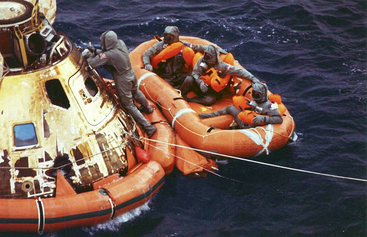In this July 24, 1969, file photo from the U.S. Navy, Lt. Clancy Hatleberg closes the Apollo 11 spacecraft hatch as astronauts Neil Armstrong, Michael Collins, and Buzz Aldrin, Jr., await helicopter pickup from their life raft after splashdown in the Pacific Ocean, 900 miles southwest of Hawaii, returning to Earth from a successful lunar landing mission. Hatleberg's mission was to decontaminate the astronauts and their command module, Columbia, immediately following splashdown. (Milt Putnam/U.S. Navy via AP, File)