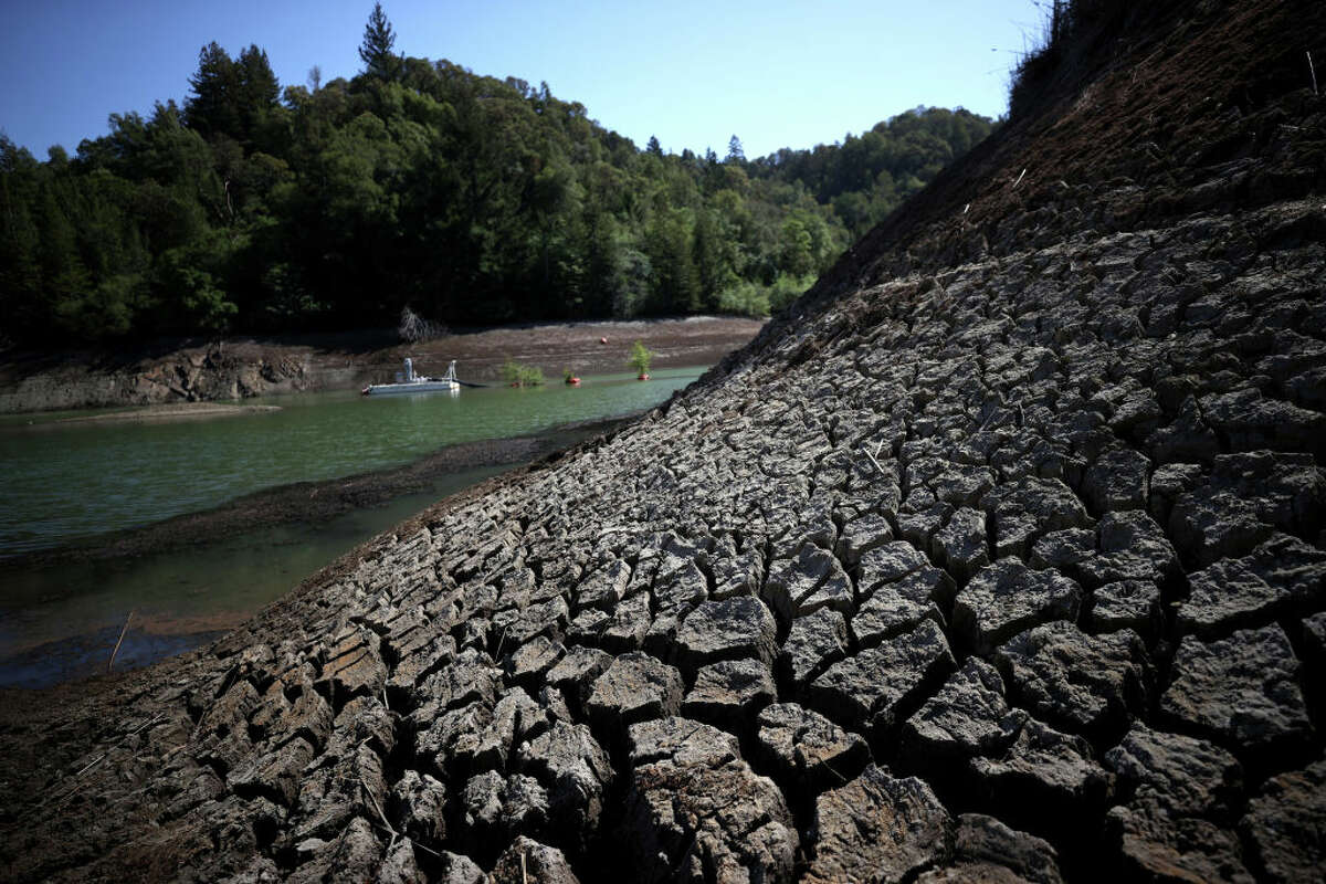Dry cracked earth is visible along the banks of Phoenix Lake on April 21, 2021, in Ross, Calif.