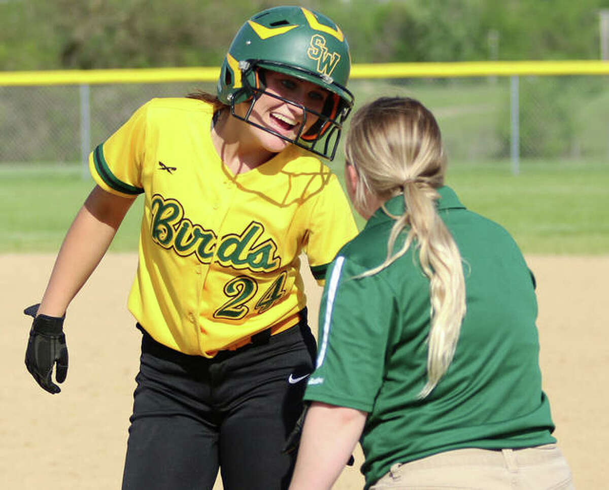 Southwestern's Josie Bouillon (left) is greeted at first base by coach Amanda Edwards after a hit during the 2019 season in Piasa. On Tuesday, Bouillon had three hits in the Birds' victory over Alton in Godfrey.