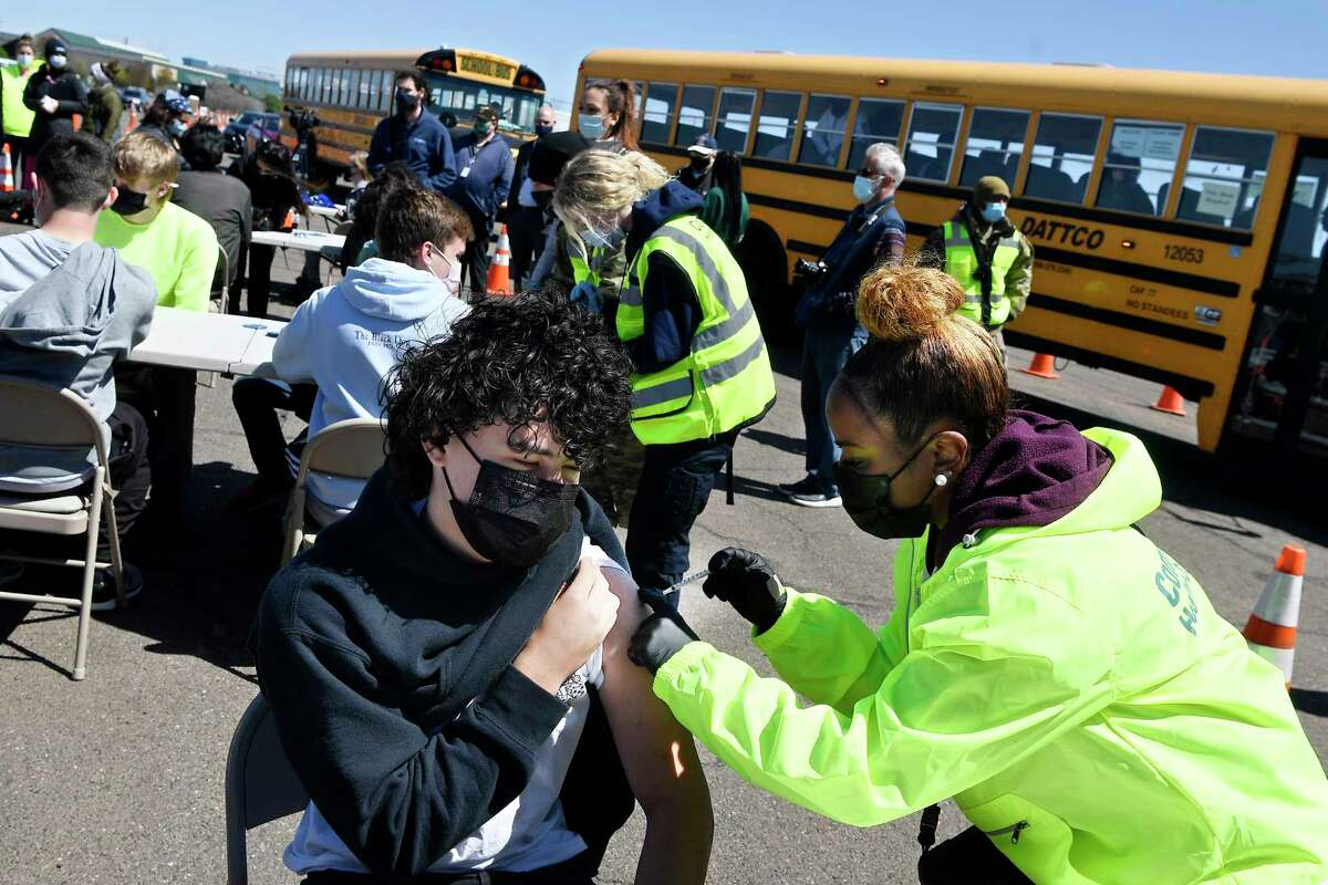People get COVID-19 vaccine shots during a mass vaccination site at the Pratt & Whitney airport runway in East Hartford last month.