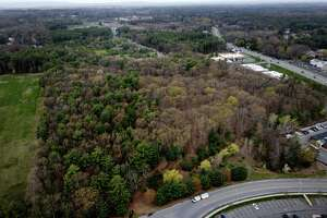 Aerial view showing the 37 acre wooded lot that will be converted onto a park on Wednesday, April 28, 2021, in Clifton Park, N.Y. The planned recreational space off Maxwell Drive, bottom, will include trails connecting to Moe Road and a parking lot for 50 cars. (Will Waldron/Times Union)