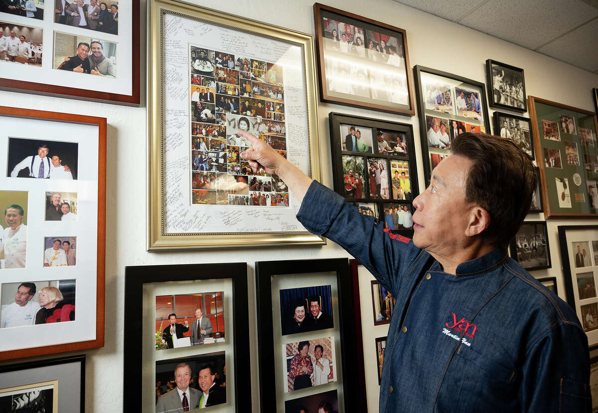 Chef Martin Yan observes the photographs memorabilia seen in his office. Yan's career launched with a cooking show in Canada in 1978 that later became