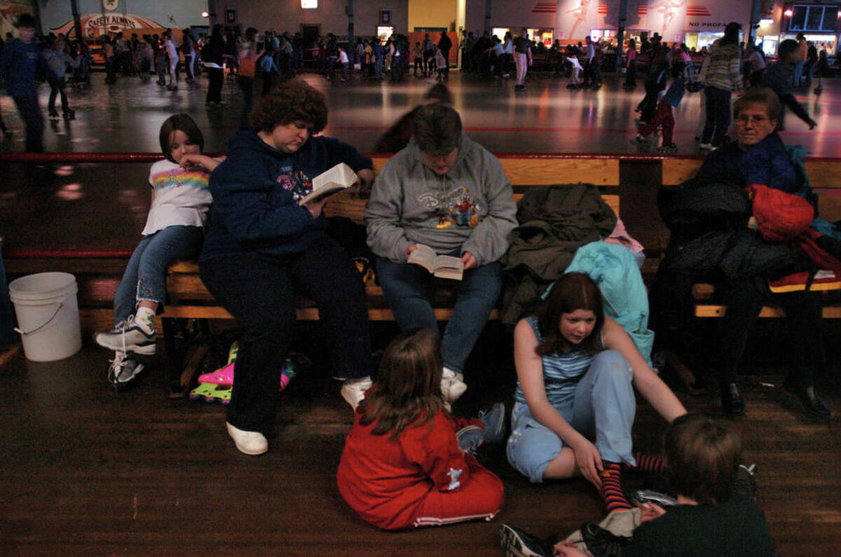 """Times Union Staff photograph by Philip Kamrass -- Tracey Cappelli of Coxsackie, left, and her sister Tammy Staley-Ross of Selkirk, right, read books while their children change out of their roller skates at Guptill's Arena in Latham, NY Sunday January 18, 2004. The women came to Guptill's as children, and used to skate. Tracey's children are Rebecca, 7, upper far left white t shirt, and Leahanne(cq), 12, blue sleeveless shirt second from right on floor. Tammy's children are Brianna, 8, red clothing on floor left, and Allyssa, 8, lower right with back of head to camera. Extra notes for Capitaland caption- Several hundred people crowded Guptill's on this particular Sunday, many parents and children endlessly circling the wooden floor, with many others eating in the restaurant across the floor. Neon signs above the floor announced the type of skate for each song. Charles """"Skip"""" Guptill genially greeted the throngs that came in from the nearly full parking lot. His family has run the rink for over 50 years. Capitaland 2004"""