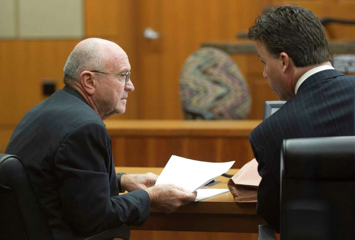 Small businessman Dave Wilson talks with his attorney Keith Gross, during a hearing at the Harris County Civil Courthouse Wednesday, Jan. 15, 2014. A judge declined to prohibit Wilson from taking his seat at the first meeting of the board of the Houston Community College. County Attorney Vince Ryan filed the December lawsuit alleging that Wilson does not live at the 34th Street warehouse he claims is his legal residence. ( Johnny Hanson / Houston Chronicle )