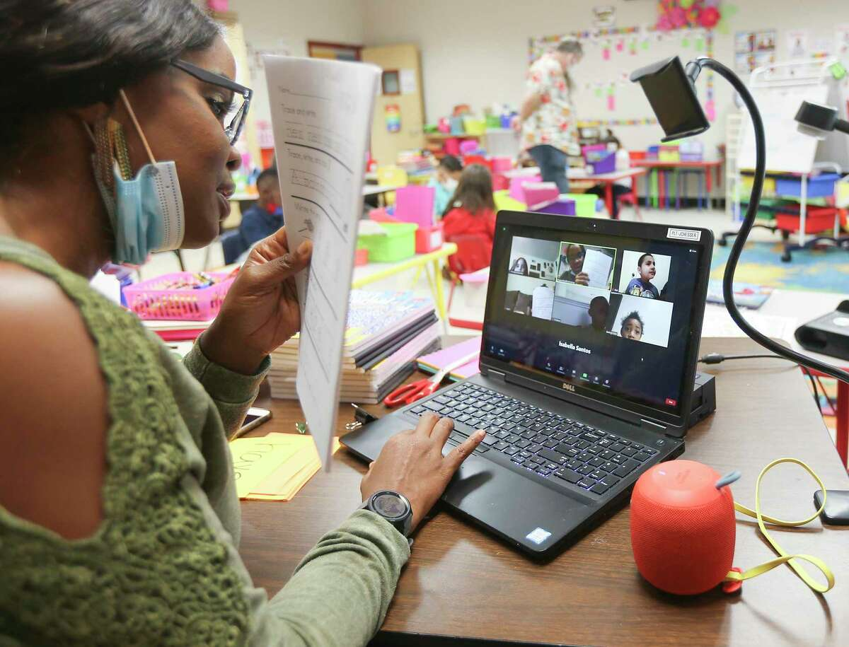 Strafford MSD kindergarten teacher Johanna Chesser teaches an online class from her classroom at Stafford Early Childhood Center while music teacher Brian Vaughn watches over her in-person class in Stafford, Texas on Tuesday, Oct. 27, 2020.