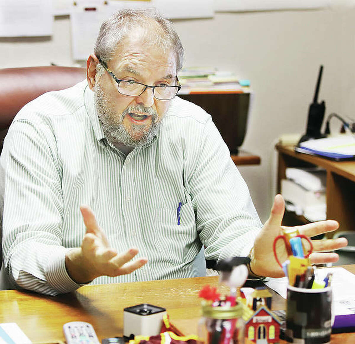 East Alton-Wood River High School Superintendent John Pearson reflects on his past and his long carrer in education from his office at the high school Wednesday. Pearson will retire from the district in June.