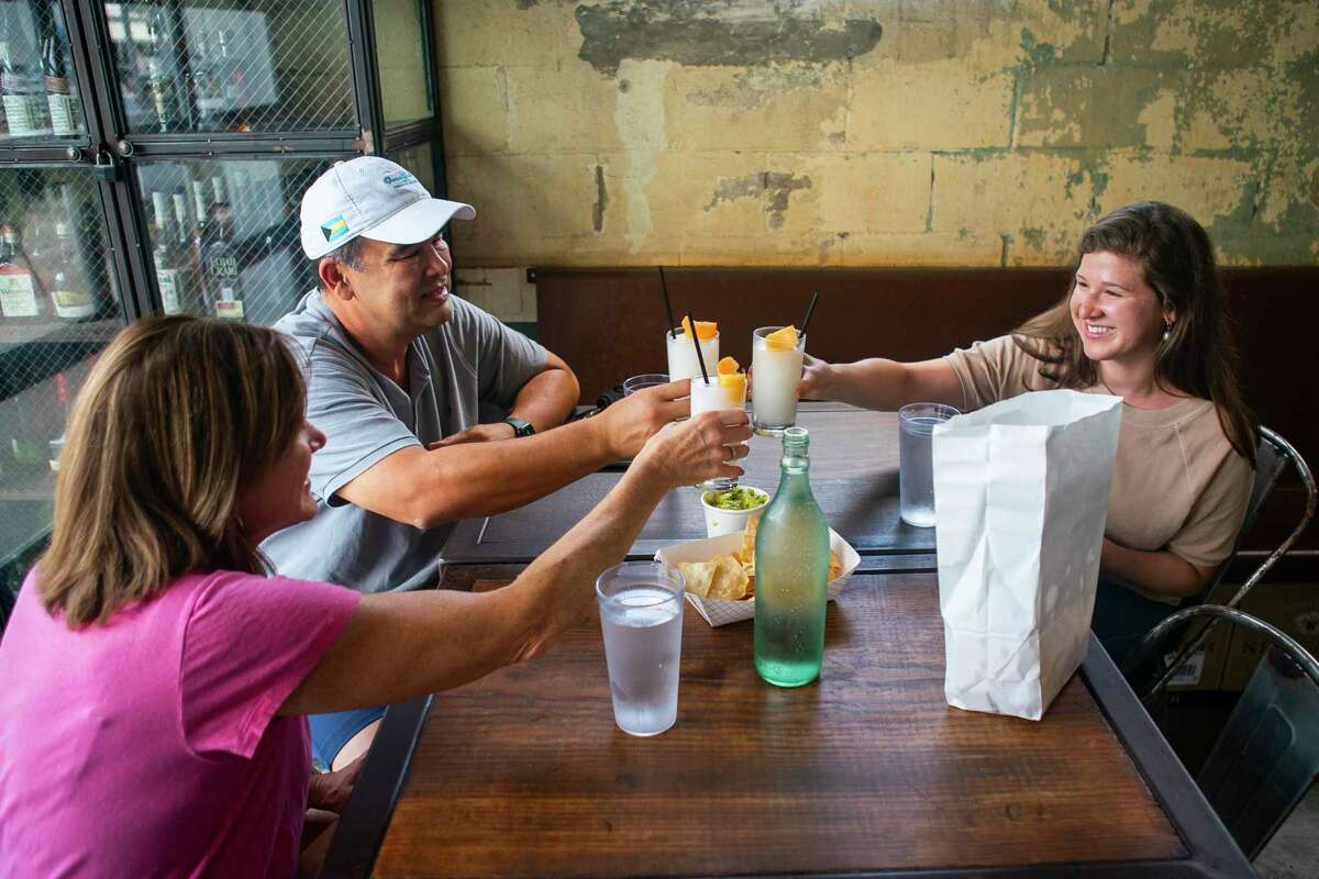 Barb and John Barajas toast with their daughter Kelsey, Friday, May 22, 2020, at Eight Row Flint in Houston. Friday was the first day that bars were allowed to reopen in Texas, and the Barajas's stopped by hoping to get something to go but decided to sit down and have a drink at the restaurant Friday afternoon.