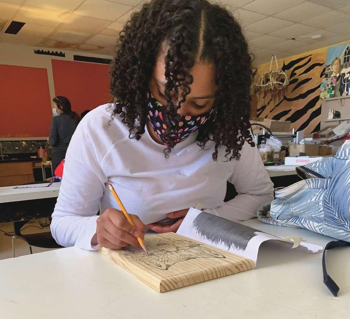 Beardstown High School senior Saivelis Garrido Crispin works on a piece of art during class.