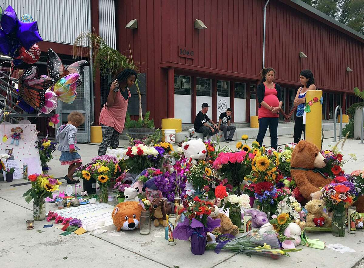 In this July 29, 2015, file photo, neighbors look at the growing memorial of flowers, stuffed animals and notes left in memory of Madyson Middleton in Santa Cruz, Calif. Adrian Gonzalez, a 21-year-old California man, pleaded guilty Tuesday, April 13, 2021, under juvenile justice terms to the 2015 murder of Middleton. Gonzalez was 15 at the time the 8-year-old was killed.