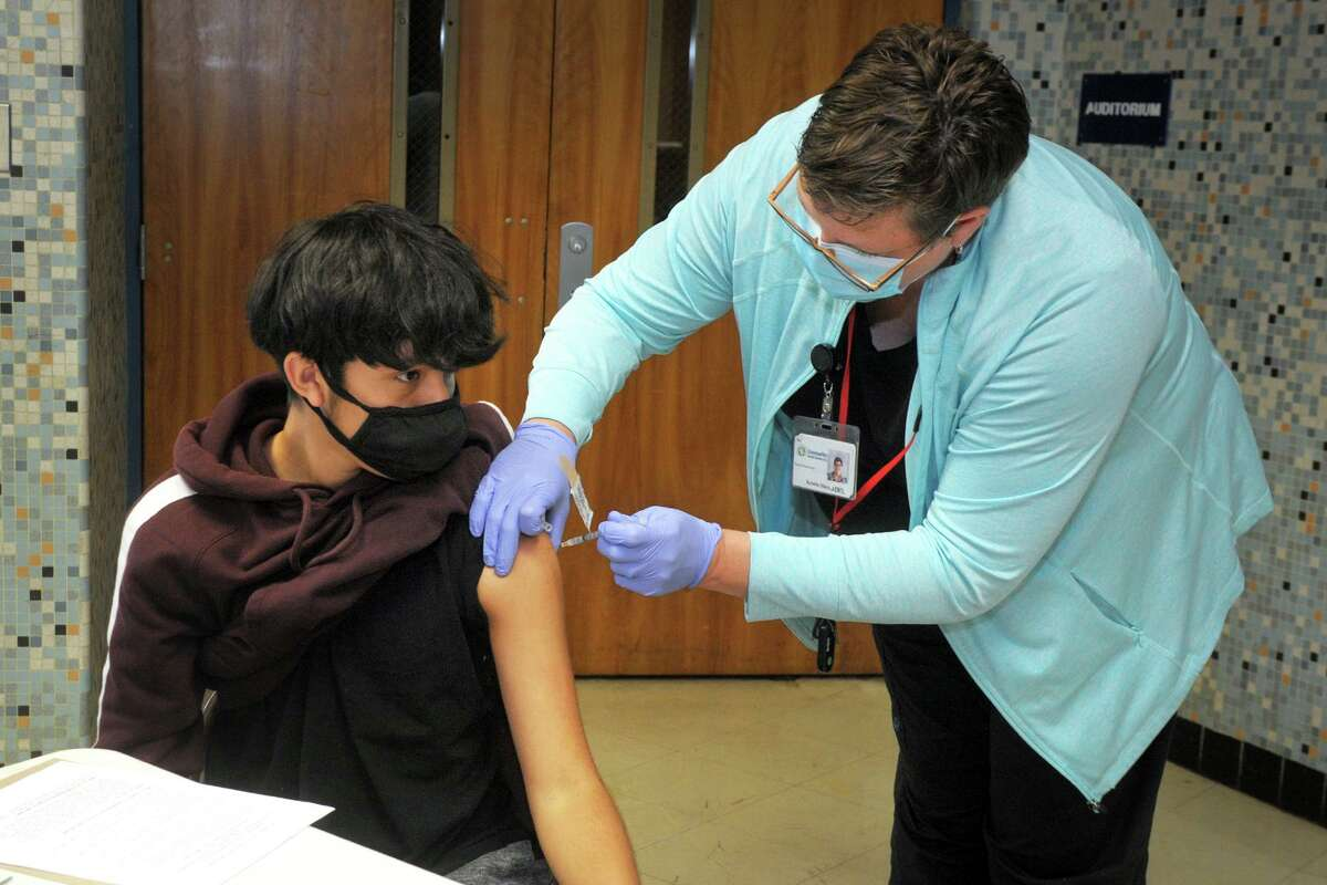 Freshman Edwin Codero receives a COVID-19 vaccination shot from nurse Kristin Sikes, of Community Health Center, during a vaccination clinic for students at Bunnell High School, in Stratford, Conn. April 28, 2021.