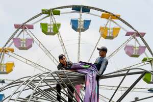 Workers set up the carnival rides, games and vendor booths Wednesday at Port Neches Riverfront Park as they prepare for the night's opening of the Port Neches River Festival that runs through the weekend. Photo made Wednesday, April 28, 2021 Kim Brent/The Enterprise