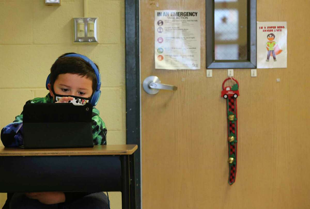 Third-grader Austin Byrom wears a headset and a mask as he takes part in a class lesson at Pearce Elementary at Southside ISD in this file photo from December. State leaders said Wednesday they will release federal funds meant to help schools cope with the effects of the coronavirus pandemic.