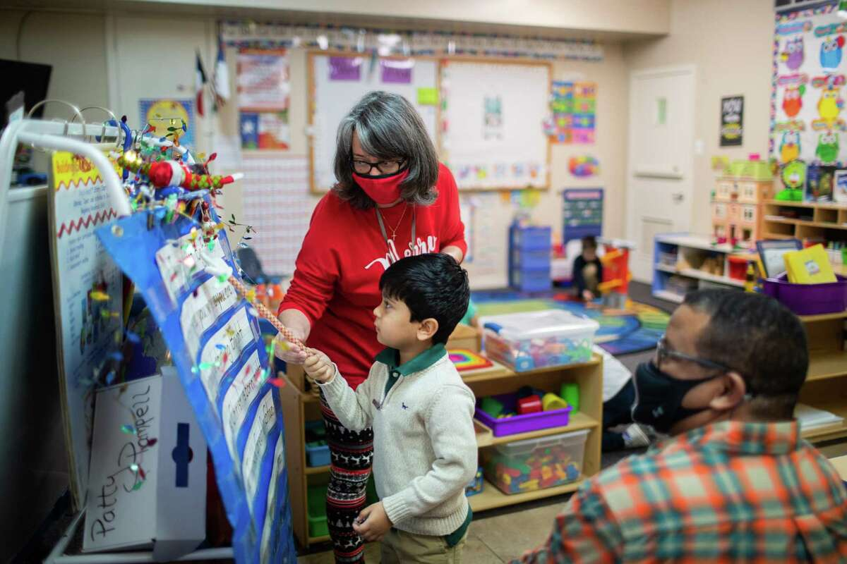 Spring Woods Christian Academy teacher Patty Pampell helps pre-k student Parth Patel, 4, with reading during class, Wednesday, Dec. 2, 2020, in Spring.