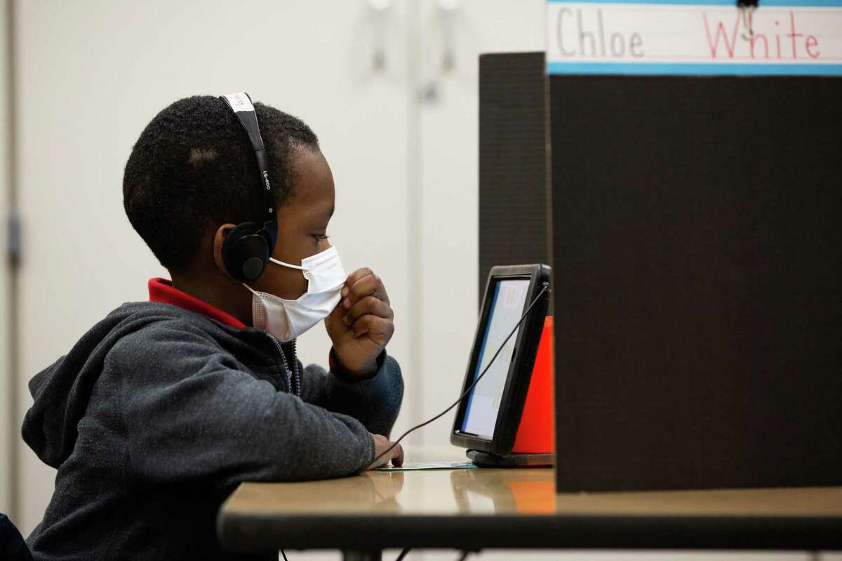 Best Elementary School kindergarten student Tyrell Billingsley works on class material on a tablet while his teacher attends to the students taking the class virtually, Thursday, Dec. 3, 2020, in Houston.