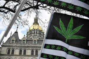 Flags with a marijuana leaf wave outside the Connecticut State Capitol building April 20, 2021 in Hartford.