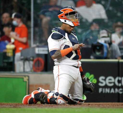 Houston Astros Martin Maldonado (15) checks his hand after colliding with Seattle Mariners Taylor Trammell (20) at home during the fourth inning of an MLB baseball game at Minute Maid Park, Wednesday, April 28, 2021, in Houston. Photo: Karen Warren, Staff Photographer / @2021 Houston Chronicle