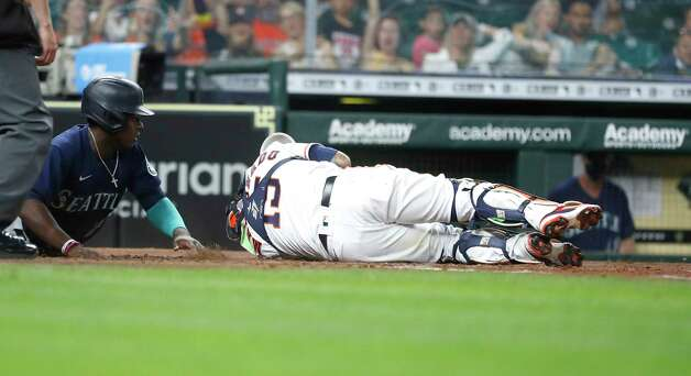 Houston Astros Martin Maldonado (15) lays on the ground after colliding with Seattle Mariners Taylor Trammell (20) who scored on Seattle Mariners J.P. Crawford's RBI double during the fourth inning of an MLB baseball game at Minute Maid Park, Wednesday, April 28, 2021, in Houston. Photo: Karen Warren, Staff Photographer / @2021 Houston Chronicle