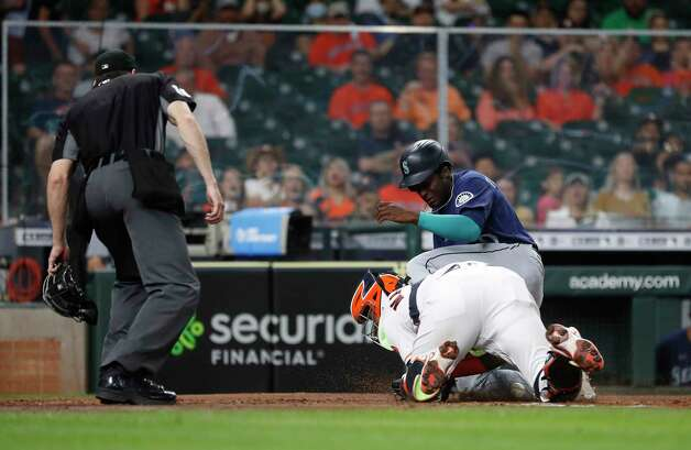 Seattle Mariners Taylor Trammell (20) collides with Houston Astros Martin Maldonado (15) at home on Seattle Mariners J.P. Crawford's RBI double during the fourth inning of an MLB baseball game at Minute Maid Park, Wednesday, April 28, 2021, in Houston. Photo: Karen Warren, Staff Photographer / @2021 Houston Chronicle