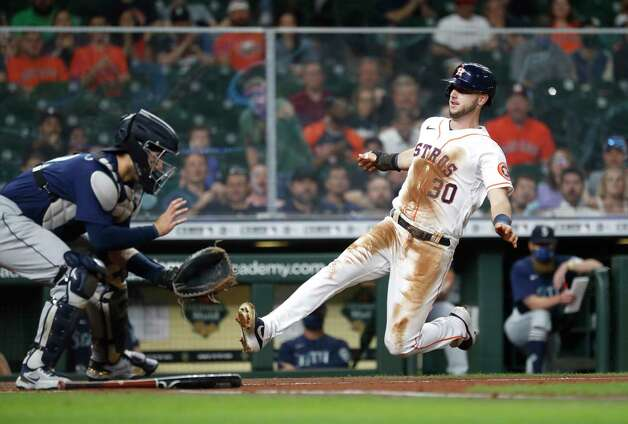 Houston Astros right fielder Kyle Tucker (30) scores a run against Seattle Mariners catcher Luis Torrens on Chas McCormick's RBI single during the second inning of an MLB baseball game at Minute Maid Park, Wednesday, April 28, 2021, in Houston. Photo: Karen Warren, Staff Photographer / @2021 Houston Chronicle