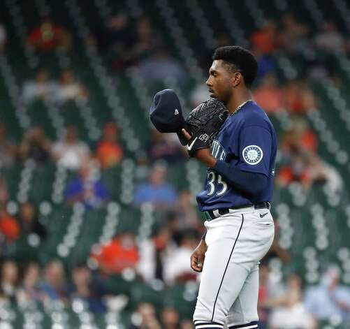 Seattle Mariners starting pitcher Justin Dunn (35) checks his cheat sheet on the inside of his hat as he pitched during the fifth inning of an MLB baseball game at Minute Maid Park, Wednesday, April 28, 2021, in Houston. Photo: Karen Warren, Staff Photographer / @2021 Houston Chronicle