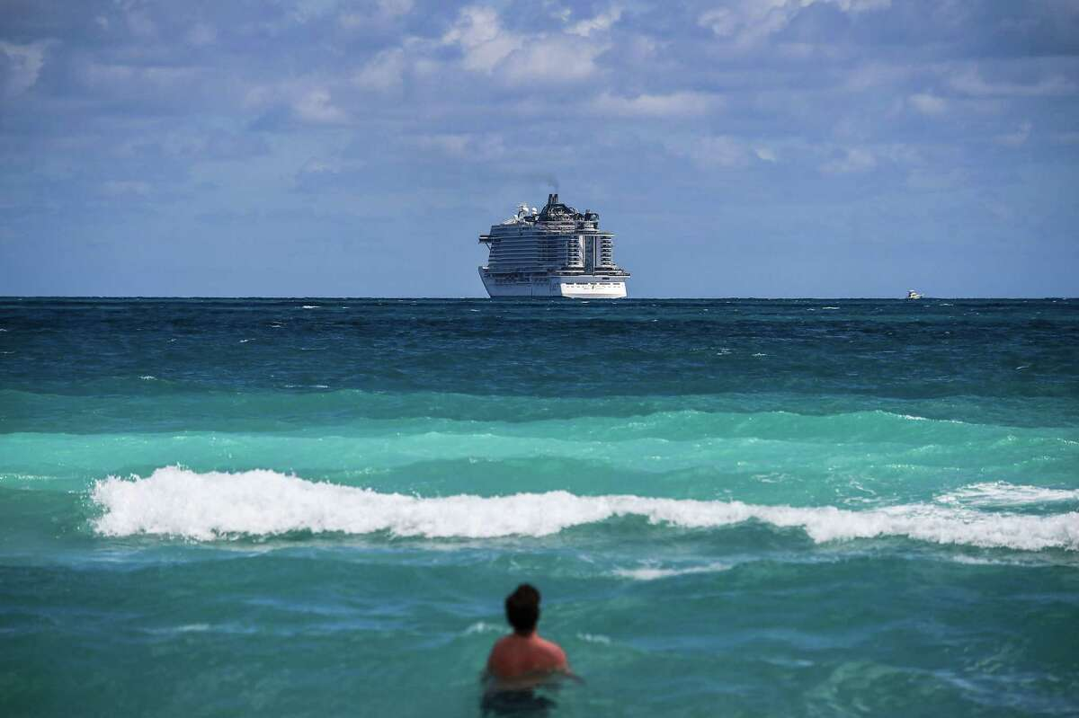 In March 2020, a cruise ship sails away from Miami Beach. Soon, vaccinated passengers can again board cruise liners - just not at U.S. ports.