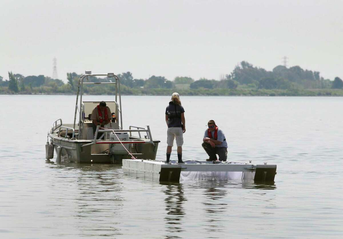 State fish and game officials position a net pen filled with chinook salmon smolts in the Sacramento River in Rio Vista in 2014, before they are released into the river. Fish from inland hatcheries will be trucked to coastal locations for release this year.