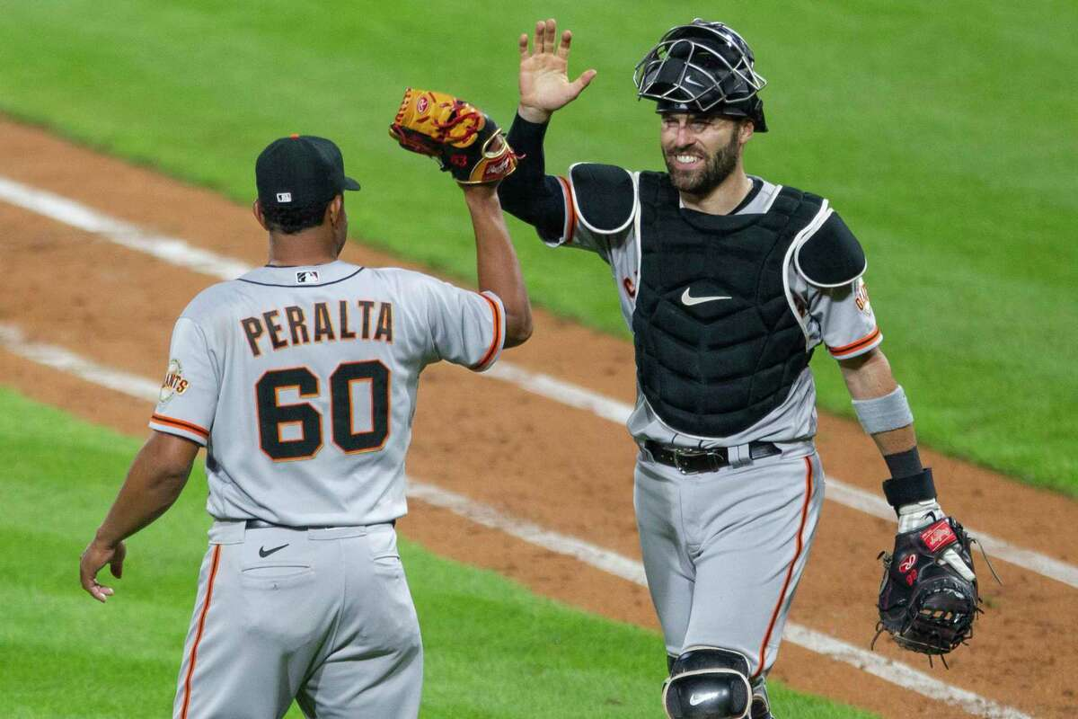 San Francisco Giants closing pitcher Wandy Peralta (60) is congratulated by catcher Curt Casali after they defeated the Philadelphia Phillies 2-0 in a baseball game, Monday, April 19, 2021, in Philadelphia. (AP Photo/Laurence Kesterson)