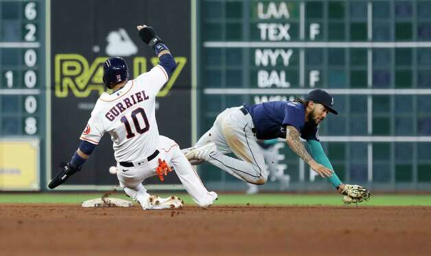 Seattle Mariners shortstop J.P. Crawford (3) misses tagging Houston Astros Yuli Gurriel (10) on a throwing error from Evan White on Carlos Correa's RBI fielder's choice during the eighth inning of an MLB baseball game at Minute Maid Park, Wednesday, April 28, 2021, in Houston. Photo: Karen Warren, Staff Photographer / @2021 Houston Chronicle