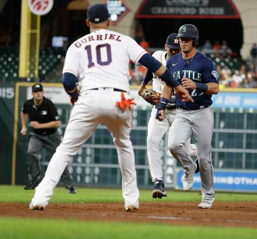 Houston Astros shortstop Carlos Correa (1) fields the ball as he and Yuli Gurriel (10) caught Seattle Mariners Dylan Moore (25) in a rundown during the eighth inning of an MLB baseball game at Minute Maid Park, Wednesday, April 28, 2021, in Houston. Photo: Karen Warren, Staff Photographer / @2021 Houston Chronicle