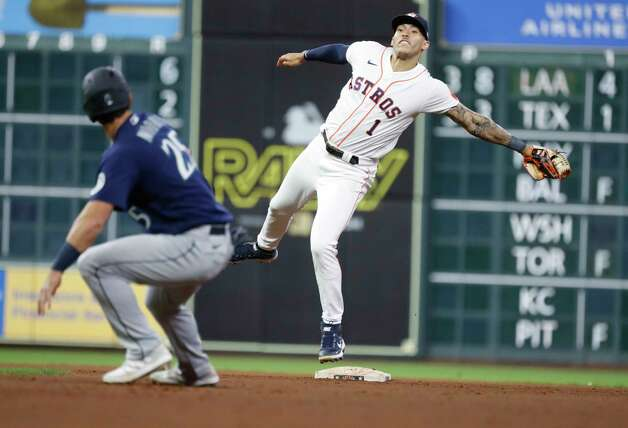 Houston Astros shortstop Carlos Correa (1) fields the ball as he catches Seattle Mariners Dylan Moore (25) in a rundown during the eighth inning of an MLB baseball game at Minute Maid Park, Wednesday, April 28, 2021, in Houston. Photo: Karen Warren, Staff Photographer / @2021 Houston Chronicle