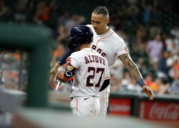 Houston Astros Carlos Correa (1) congratulates Jose Altuve after his sac fly scored Aledmys Diaz during the eighth inning of an MLB baseball game at Minute Maid Park, Wednesday, April 28, 2021, in Houston. Photo: Karen Warren, Staff Photographer / @2021 Houston Chronicle
