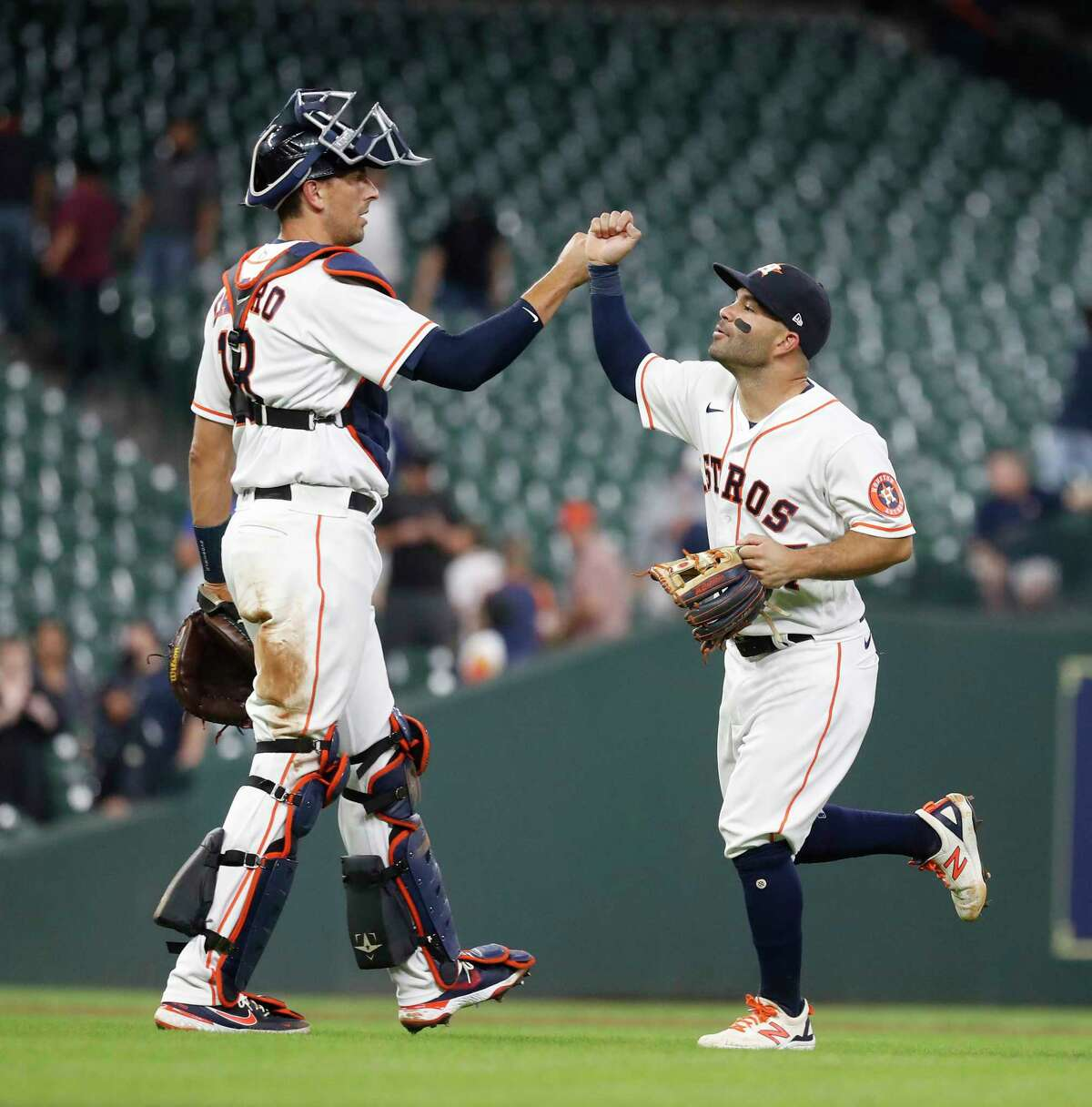 Houston Astros Jose Altuve (27) high fives catcher Jason Castro (18) after Seattle Mariners J.P. Crawford ground out to end an MLB baseball game at Minute Maid Park, Wednesday, April 28, 2021, in Houston. Astros came from behind to beat the Seattle Mariners 7-5.