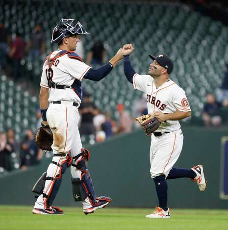 Houston Astros Jose Altuve (27) high fives catcher Jason Castro (18) after Seattle Mariners J.P. Crawford ground out to end an MLB baseball game at Minute Maid Park, Wednesday, April 28, 2021, in Houston. Astros came from behind to beat the Seattle Mariners 7-5. Photo: Karen Warren, Staff Photographer / @2021 Houston Chronicle