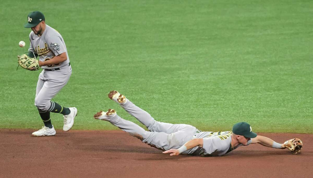 A's shortstop Vimael Machin backs up diving third baseman Matt Chapman on an infield hit by Yandy Diaz in the fourth inning. The next batter lined into an inning-ending double play.
