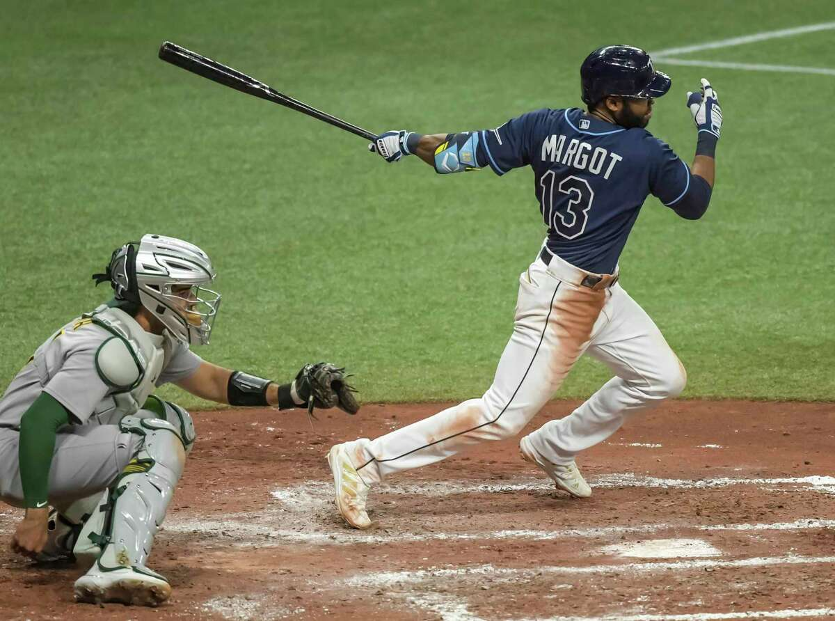 Tampa Bay Rays' Manuel Margot follows through on an RBI single next to Oakland Athletics catcher Aramis Garcia during the fifth inning of a baseball game Wednesday, April 28, 2021, in St. Petersburg, Fla. (AP Photo/Steve Nesius)